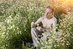 Man  sits in the field of camomiles guesses on a camomile Stock Photo