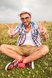 Man sits on a field  and makes the victory sign Stock Photo