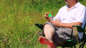 A man sits in a folding picnic chair and drinks water. Closes the bottle and puts it in the stand. stock video footage