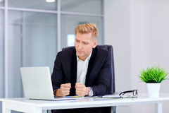 A man sits in front  blond frustrated laptop at his deskthe offi Royalty Free Stock Images