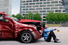 Man sits in front of a damaged car Royalty Free Stock Image