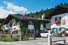 Man sits in front of the traditional bavarian house in Mittenwald, Germany. Stock Photo