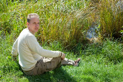 The man sits in a grass Royalty Free Stock Photography