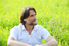 Man sits in the grass in the summer. A man sits in the  grass in the summer Royalty Free Stock Image