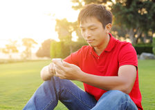 Man sits on grass Stock Photo
