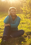 Man sits on grass and use mobile phone Royalty Free Stock Photo