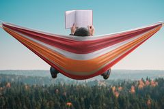 A man sits in a hammock and reads a book in a picturesque place. Back view. stock image