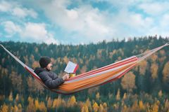A man sits in a hammock and reads a book in a picturesque place. Mug in his right hand. stock image
