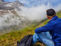 A man sits on a hillside and admires the tops of mountains in the clouds royalty free stock images