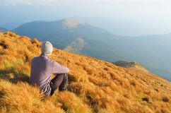 Man sits on a hillside. Autumn Landscape with a man sitting on the hillside. Outdoor recreation Stock Photos