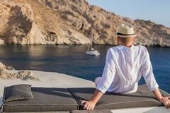 A man sits with his back on the shore of the bay and looks at the cliffs and the blue sea. The male back silhouette in the hat enjoys a view of the rocky coast Stock Photos