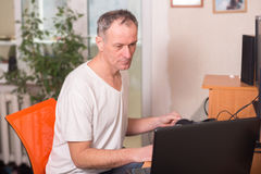 Man sits between a laptop and a computer, looking at the screen Stock Photography