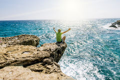 A man sits on a ledge of rock above the sea at Cape Greco . Cypr Stock Photos