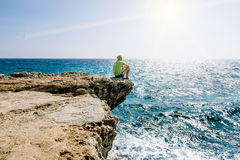 A man sits on a ledge of rock above the sea at Cape Greco . Stock Photo