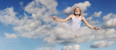 Man sits in lotus position on cloud Stock Photos