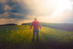 Man sits in a meadow looking at a cross of light like a miracle. Man waiting for a miracle in the meadow stock image