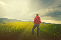 Man sits in a meadow looking at a cross of light like a miracle. Man waiting for a miracle stock images