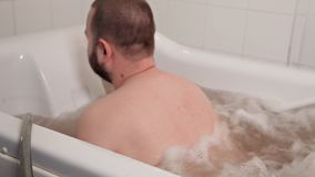 A man sits in a medicinal bath oils, a girl employee at a Spa, getting a massage from hot water, a special technique, a stock video