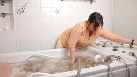A man sits in a medicinal bath oils, a girl employee at a Spa, getting a massage from hot water, a special technique, a stock footage