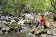 Man sits at the mountain river Royalty Free Stock Images