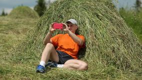 Man sits near haystack and makes photos on his smartphone stock video