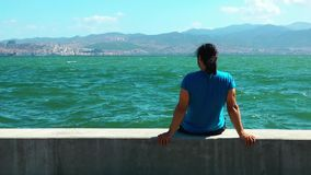Man sits near the seaside. And the city Izmir Turkey video stock footage