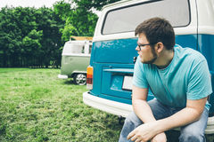 Man sits near van and thinks about something. Backbag in his hands Stock Images