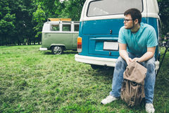 Man sits near van and thinks about something. Backbag in his hands Royalty Free Stock Photography