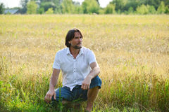 Man sits near a wheat field Royalty Free Stock Images