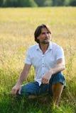 Man sits near a wheat field Stock Photo