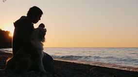 A man sits next to his dog, watching together the sunset over the lake or the sea
