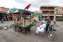 A man sits next to his portable stall at Djemaa el-Fna, the main square in the Marrakesh medina in Morocco. Royalty Free Stock Photography