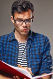 Man sits and notes in a notebook. Attractive man sits and notes in a notebook Royalty Free Stock Image