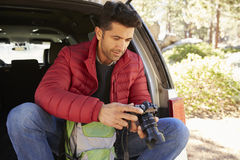 Man sits in the open back of car in forest checking camera Royalty Free Stock Photography