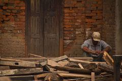 A man sits outside his now earthquake ruined house in Bhaktapur, Stock Photography