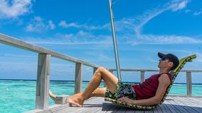 Man sits in over water bar on luxury island resort in Maldives. royalty free stock photo