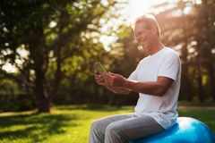 A man sits on a ball for yoga and looks at something on his tablet. He smiles. A man sits in a park on a blue bowl for yoga. He is looking at something on his Stock Photo