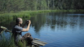 A man sits on a pier of the lake and making photo on the phone. The beautiful blue lake and forest on background stock video