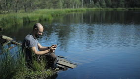 A man sits on a pier of the lake and play on tablet in game. The beautiful blue lake and forest on background stock footage