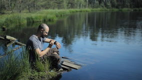 A man sits on a pier of the lake and touch smartwatch. The beautiful blue lake and forest on background stock footage