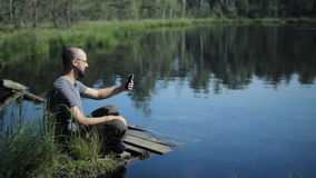 A man sits on a pier of the lake and is video calling on the phone. The beautiful blue lake and forest on background stock footage
