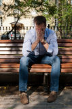 Man sits in the public garden Royalty Free Stock Image