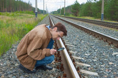 Man sits on railway with magnifier in hand Royalty Free Stock Photo