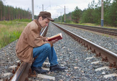 Man sits on railway and with reads Royalty Free Stock Image
