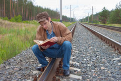 Man sits on railway and with reads Royalty Free Stock Photos