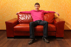 man sits on red leather sofa royalty free stock image