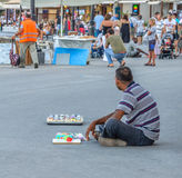 Man sits on the road and sells souvenirs Royalty Free Stock Photos