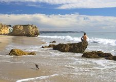 Man Sits on Rock on Beach in Malibu California. Lone man sits on rock along El Matador State Beach in California looking out to sea Stock Photos