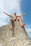 Man sits on rock, bottom view Stock Photography