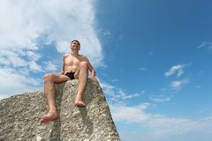 Man sits on rock, bottom view Royalty Free Stock Photography